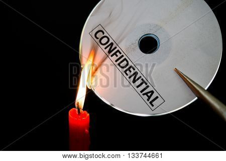 burning a confidential compact disc with candle in dark
