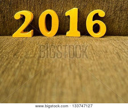 Text of gold 2016 make from wood. Golden year 2016. New year decoration closeup on 2016 text. Happy new year 2016. Gold 2016 on brown velvet with copy space at the bottom for your text.