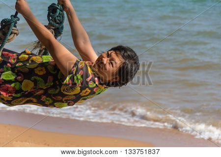 Asia Woman Posing On Swing At Beach With Blue Sea And Sky