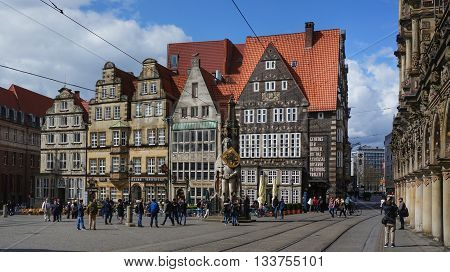 Bremen, Germany, 17th April 2016. People, mainly tourists, on the main market square with the famous statue of 'Roland of Bremen' in the middle of it and historic buildings in the background.