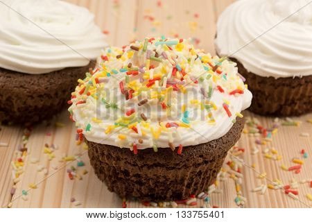 Muffin with cream and colorfull crumbs on top of it sitting on bright wooden table