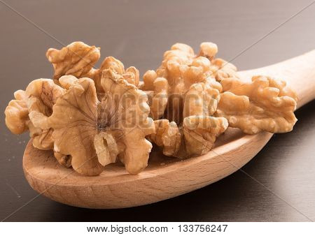 Big shelled walnuts on a wooden spoon in black background