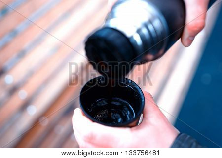 Filling cup with hot tea from thermos bokeh background