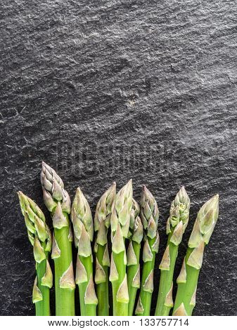 Green young asparagus sprouts on the black background.