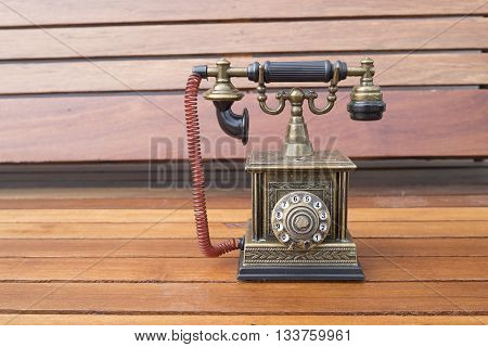 Lighter in retro classic phone model vintage old dial Telephone on wood background