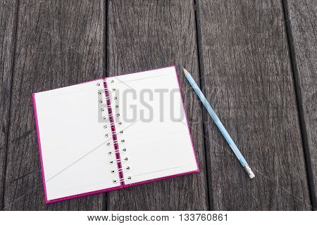 Opened white page of blank realistic spiral notepad notebook and blue pencil on wood texture background