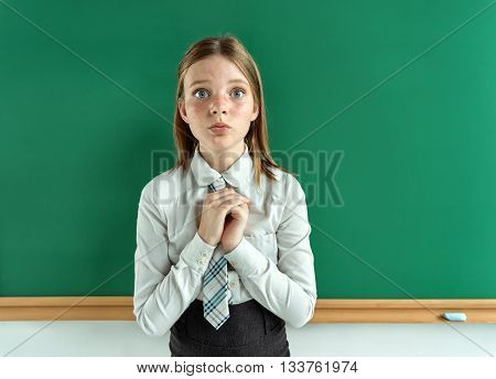 Cute schoolgirl near blackboard with folded hands in anticipation of something. Photo of teen school girl creative concept with Back to school theme
