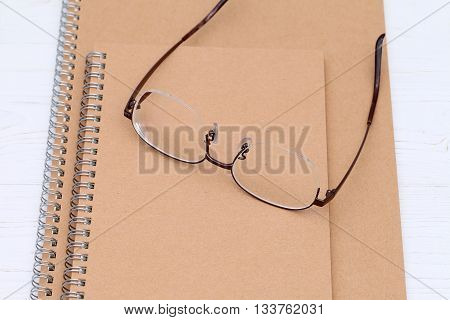 Glasses and notebook on the white wooden table