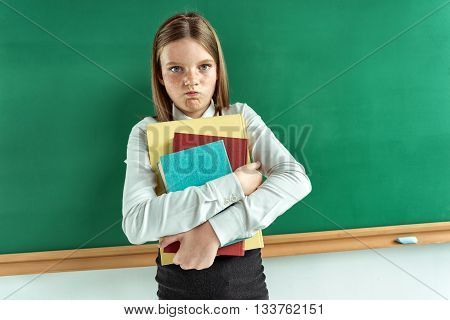 Resentful little girl hugging school books. Photo of teen school girl creative concept with Back to school theme