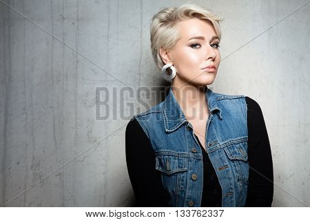 Portrait Of A Woman With Short Hair In Jeans Jacket With Large Earrings On A Gray Cement Background