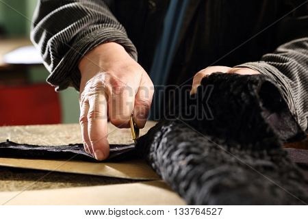 The tailor cuts a template dress leather knife tailoring