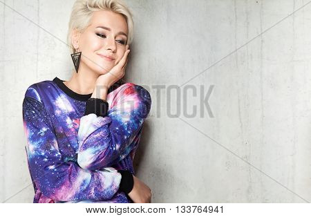 Fashion Young Woman With Short Hair Wearing In Sweatshirt With Space Print On The Cement Wall Backgr
