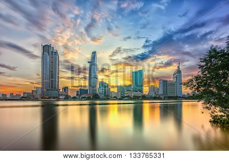 Ho Chi Minh City, Vietnam - June 9th, 2016: Riverside City sunset clouds in the sky at end of day brighter coal sparkling skyscrapers along beautiful river in Ho Chi Minh City, Vietnam