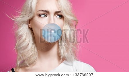 Blonde Girl Inflates A Bubble Of Gum Blue On A Pink Background