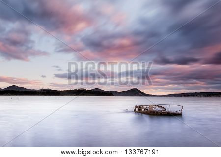 Sunken boat in the lake at sunset