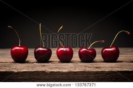 Five delicious big cherries on a rustic wooden table