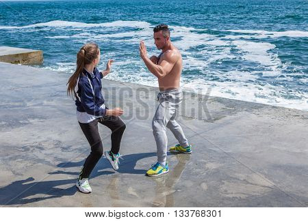 trainer with the schoolgirl who is engaged in karate on the seashore
