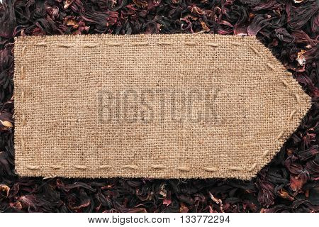 Pointer of burlap lying on a dry hibiscus background with place for your text
