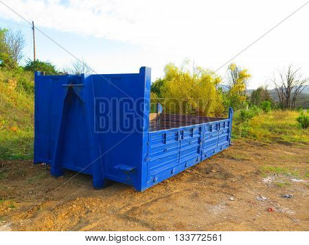 Empty blue builders skips on wasteland near Alora Andalusia