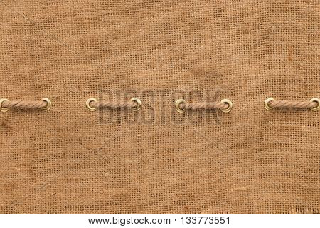 Burlap with one lines of rope and gold rings with space for your text