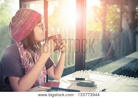 asian younger woman and hot coffee mug in hand smiling with happiness emotion sitting beside mirror window against beautiful sun light process warming color mood and tone