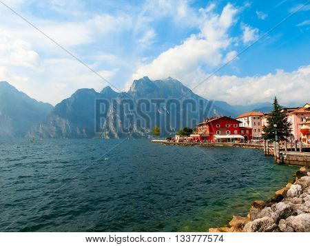 Torbole, Italy - September 21, 2014: Lake Garda boardwalk with houses, tourists and boats in Torbole, Italy. Torbole is one of the most popular towns on Garda Lake, known as a wind surfers paradise.