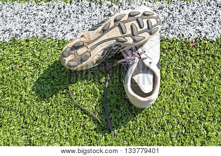 Old Soccer Shoes On Artificial Turf Field With White Marking Line