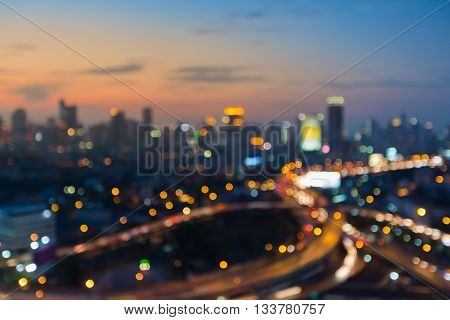 Night blurred light highway overpass with city downtown sunset sky background