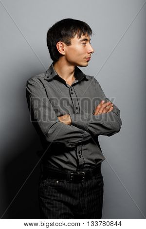Young man in steel-blue shirt standing on grey background in thoughtful pose