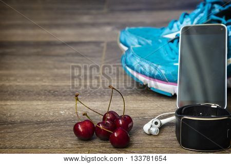 Sport shoes and smart watch with set for sports activities on floor.