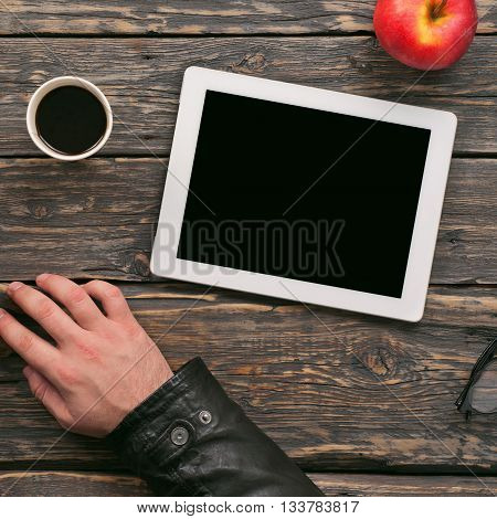 Tablet with blank screen on a dark wooden table top view. Man using tablet works outside the office