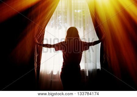 Silhouette of a young woman opens curtains at window.