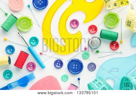 Sewing kit on the white background. Colorful set consisting of measuring tape ruler pins buttons bobbins pencils.