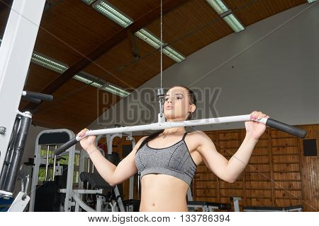 Beautiful young body builder doing arms exercises on trainer in the gym
