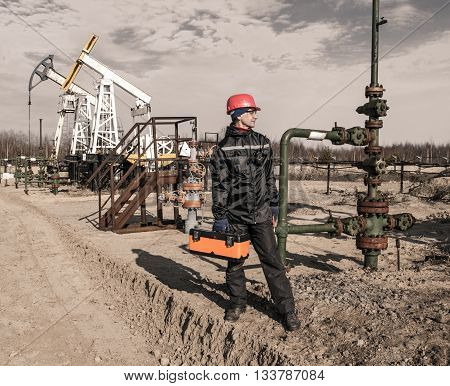 Man engineer in the oil field wearing red helmet and work clothes holding toolbox and wrenches in his hand and radio in jacket pocket. Pump jack and wellhead background. Oil and gas concept. Toned.