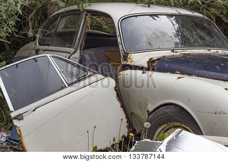 A rusty and destroyed old-fashioned car among a pile of rubbish.