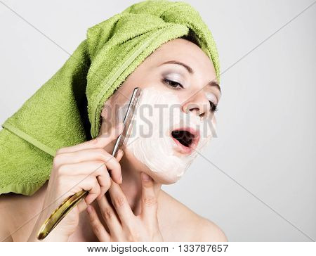 beautiful Young woman dressed in a bath towel shaves with a straight razor. beauty industry and home skin care concept, extreme Beauty.