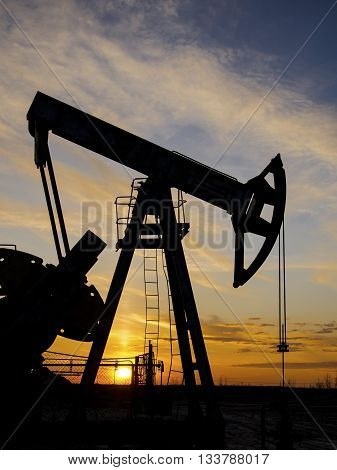 Pump jack silhouette during sunset on the oilfield. Oil and gas concept.