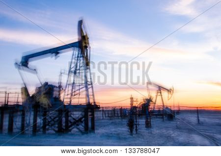 Blurry pump jacks silhouettes during sunset on the oilfield. Oil and gas concept.