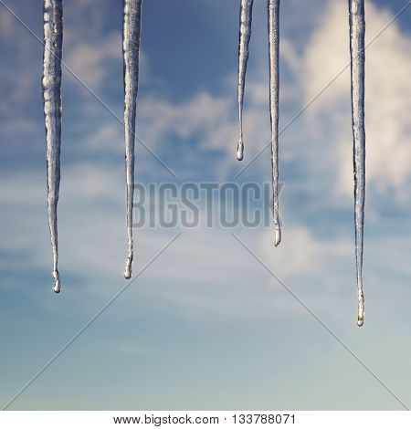 Icicles in bright sunshine against a blue sky with clouds.