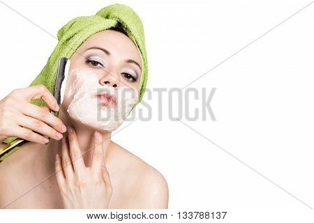 beautiful Young woman dressed in a bath towel shaves with a straight razor. beauty industry and home skin care concept, extreme Beauty. isolated on white background.
