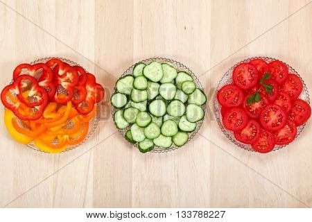 Sliced vegetables in the dishes on a wooden table.