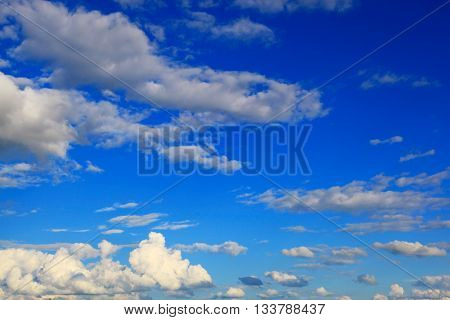 Blue sky with the white cumulus clouds.