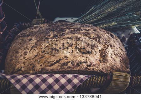 Vintage style: Homemade gluten-free and yeast free bread craft close-up in wicker basket with ears of barley wrapped in a plaid napkin