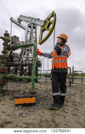 Woman engineer in the oil field talking on the radio wearing orange helmet and work clothes. Pump jack background. Oil and gas concept.