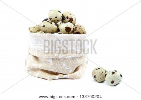 Quail eggs in a canvas bag isolated on white background.