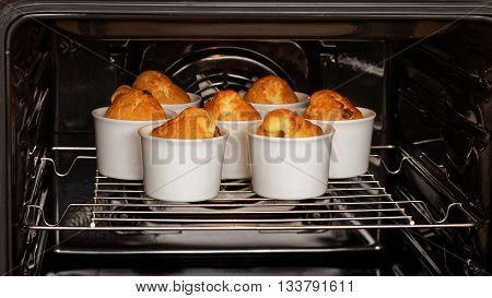 Homemade cupcakes in white ceramic mold is baked in the oven