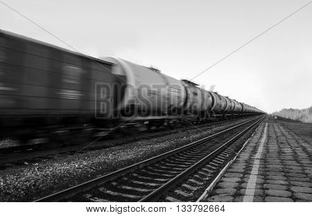 Train with oil tanks moving. Transportation of fuel on the railroad. Black and white shot.