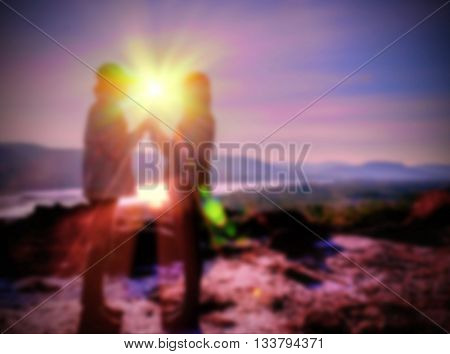 Abstract Blurred and soft photo of the lover standing on the hilltop during sunrise.