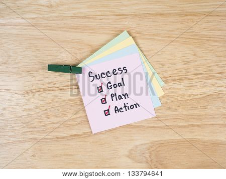 Handwriting word Success Goal Plan Action on colorful notepaper with wood background (Business concept)